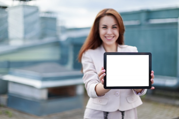 Pretty businesswoman in beige suit stand on the roof and hold empty tablet