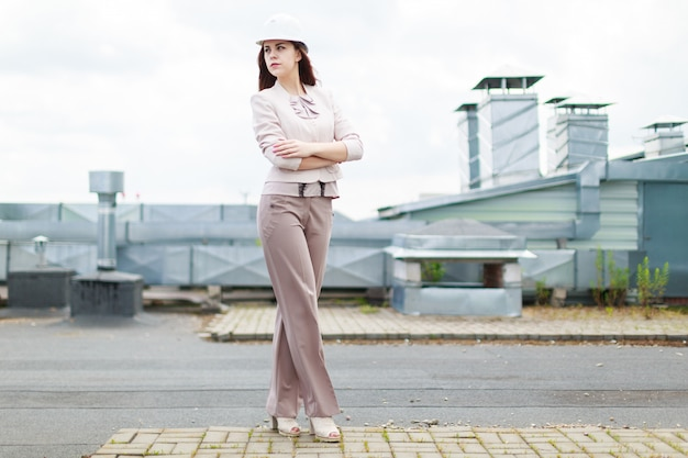 Pretty businesswoman in beige suit stand on the roof