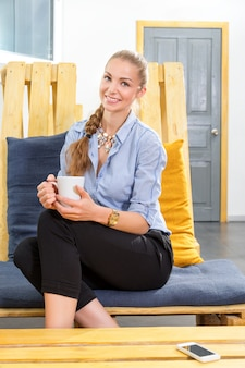 Pretty businesswoman drinking hot morning coffee and dreaming in modern loft. woman in businness. freelancer in coworking center is resting and enjoying the drink. freelance work concept.