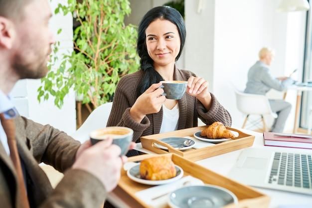 会議でコーヒーを楽しんでいるかなりの実業家