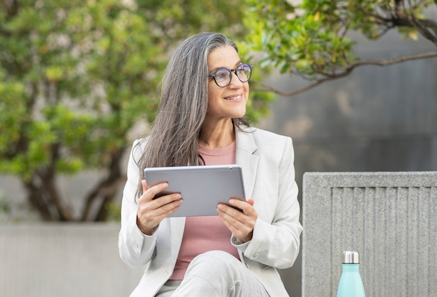 Pretty businesswoman in financial zone with tablet