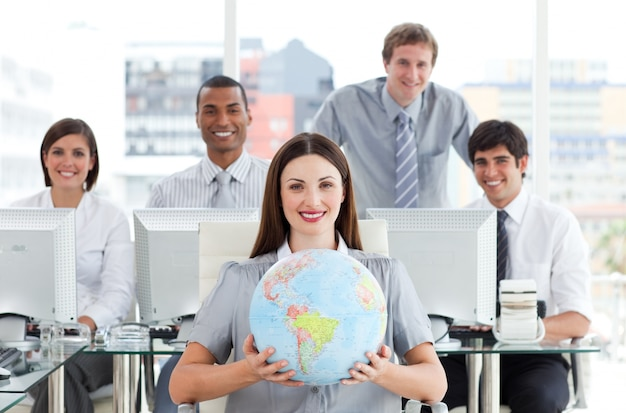 Pretty businesswoman and her team showing a terrestrial globe