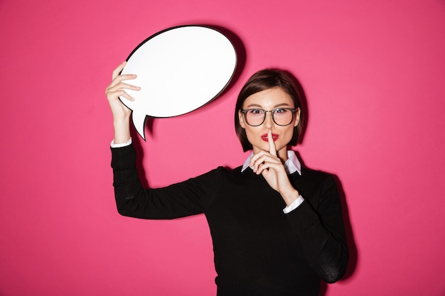 Pretty businesswoman holding speech bubble and showing speech bubble isolated