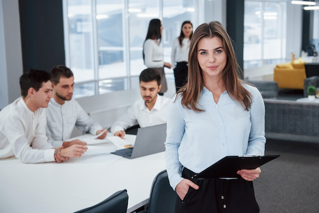 Pretty businesswoman. portrait of young girl stands in the office with employees at background
