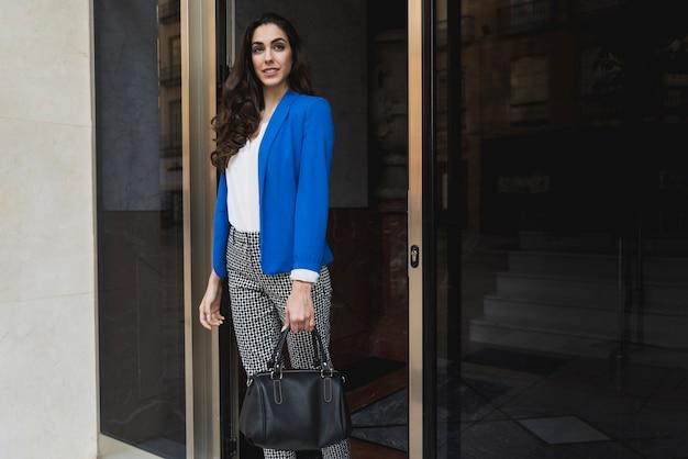 Pretty businesswoman posing next to a glass door
