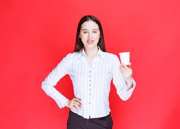Довольно предприниматель позирует с пластиковой чашкой чая на красном фоне.