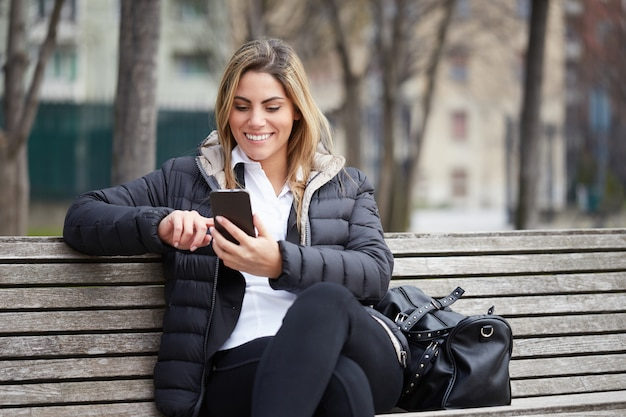 Pretty businesswoman talking to mobile in urban environment sitting on a bench