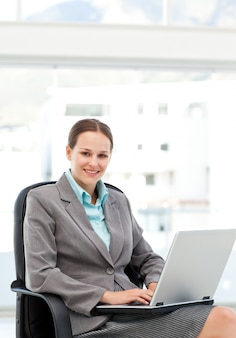 Pretty businesswoman working at her desk with a laptop
