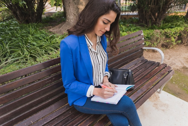 Pretty businesswoman working on a park bench Free Photo
