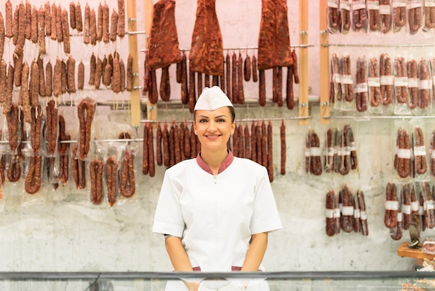 Симпатичная мясная женщина, работающая в мясной лавке.