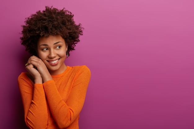 Donna abbastanza calma con acconciatura afro, guarda delicatamente da parte, tiene le mani vicino al viso