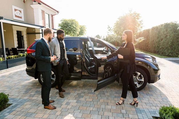 Pretty car saleswoman in business wear helping to young two multiethnical businessmen clients to make decision showing a new car, opening car doors, while standing on the yard of car salon outdoors