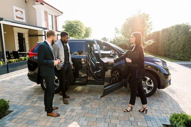 Довольно продавщица автомобилей в деловой одежде помогает двум молодым клиентам-бизнесменам принимать решение, показывая новую машину, открывая автомобильные двери, стоя на дворе автомобильного салона на улице.