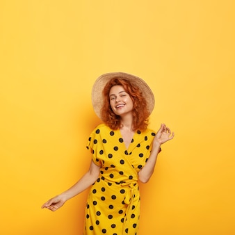 Pretty carefree redhead woman posing in yellow polka dress and straw hat