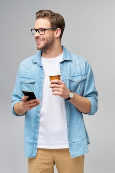 スタジオの灰色の壁の上に立って行くために彼の電話とコーヒーのカップを保持しているブルージーンズのシャツを着たかなりカジュアルな男