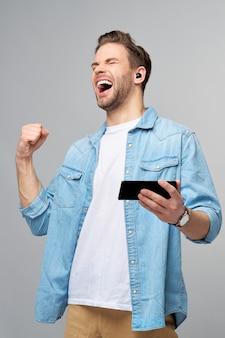 Довольно случайный мужчина в синей джинсовой рубашке держит телефон над серой стеной студии
