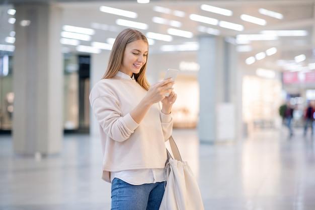 大規模な現代的なショッピングモールや貿易センター内のオンライングッズを検索しながらスマートフォンでスクロールするかなりカジュアルな女性