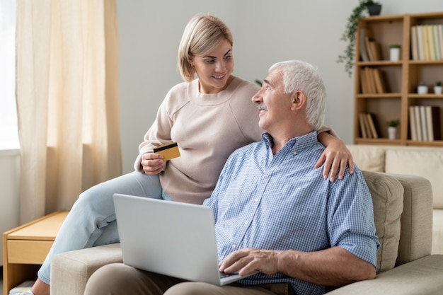Pretty casual woman with credit card looking at her retired father with laptop while both shopping online at home