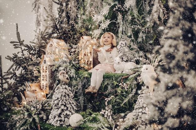 Il bambino abbastanza caucasico con i capelli biondi lunghi sorride e si siede nell'atmosfera di natale con un piccolo coniglio