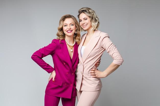 白とピンクのスーツのかなり白人の女性の友人は笑顔、灰色の壁に分離された画像