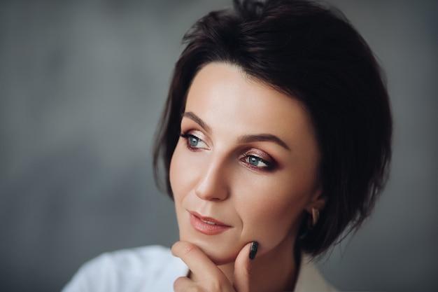 Modello femminile abbastanza caucasico con i capelli corti isolato su sfondo grigio studio