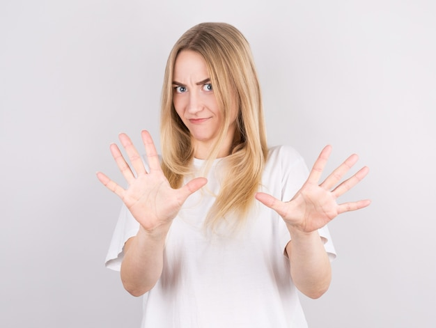Pretty caucasian female with serious expressions asks you to be calm and attentive. stop sign.