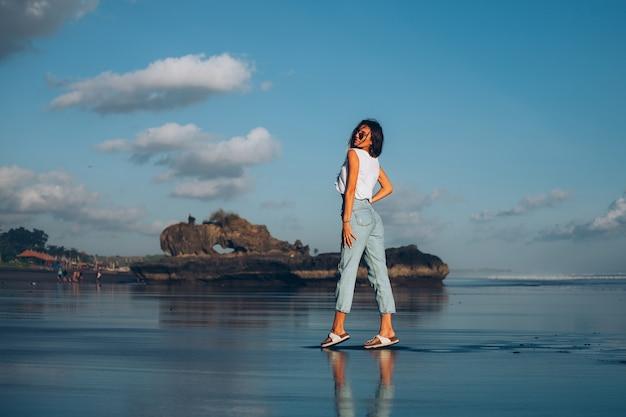 夕焼けの光で海のそばのビーチを反射する白いトップとジーンズのかなり白人のフィット女性