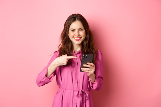 Pretty caucasian girl advertising online offer, pointing finger at her smartphone and smiling satisfied, recommending app, standing over pink wall.