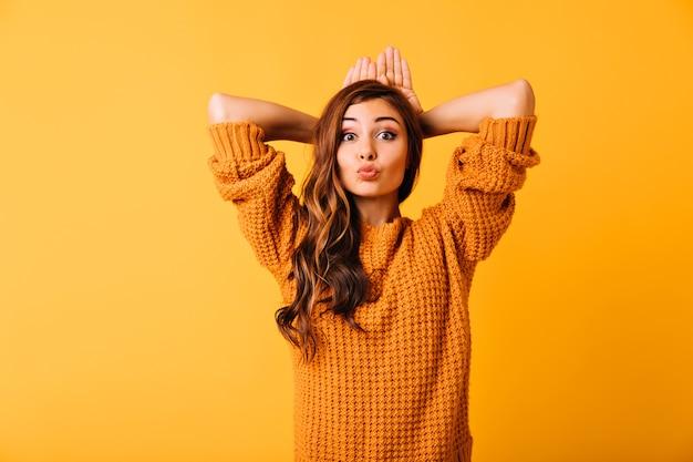 Довольно кавказская девушка в ярком свитере позирует с выражением лица поцелуи. приятная кудрявая женщина наслаждается портретной съемкой на оранжевом.