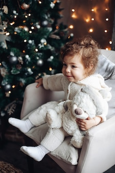 Симпатичная кавказская девушка с вьющимися волосами сидит возле большой красивой елки и расслабляется
