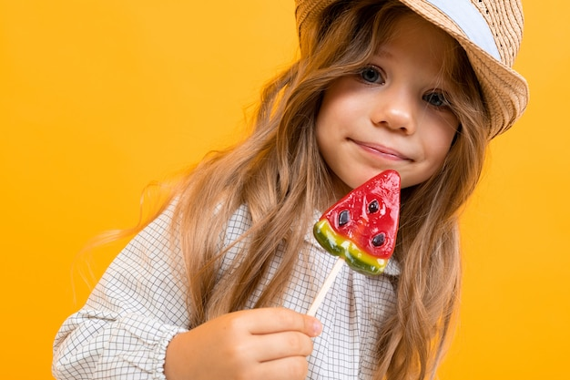 Pretty caucasian girl with hat holds watermelon lolipop and phone on yellow wall