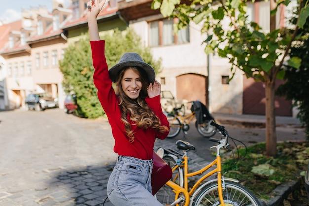 Signora abbastanza caucasica che esprime emozioni divertenti durante il giro in bicicletta intorno alla città d'autunno