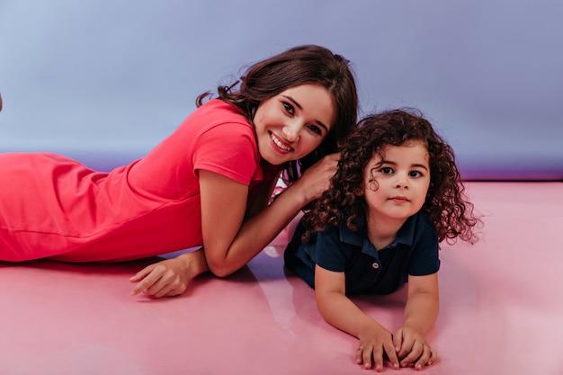 彼女のかわいい娘と一緒に横たわっているかなり白人の女性。床にポーズをとって笑顔のブルネットの姉妹の屋内写真。