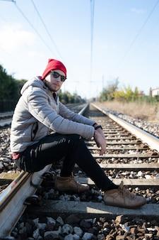 예쁜 백인 남성 모델은 겨울 날 기차 트랙에 앉아있다. 그는 선글라스를 쓰고 미래에 대해 사려 깊고 걱정합니다.