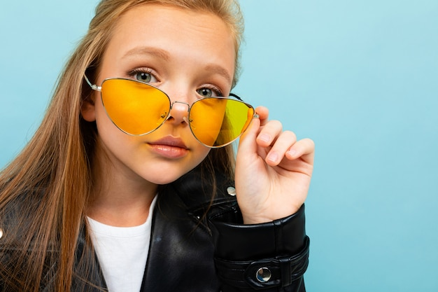 Pretty caucasian teenager girl with long brown hair in black jacket and denim jeans holds yellow sunglasses isolated on blue