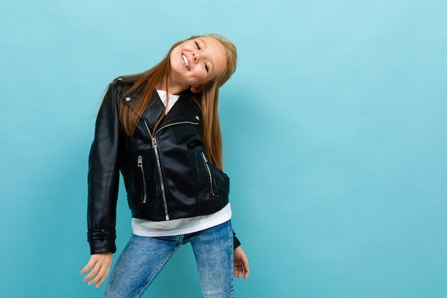 Pretty caucasian teenager girl with long brown hair in black jacket and denim jeans smiles isolated on blue background