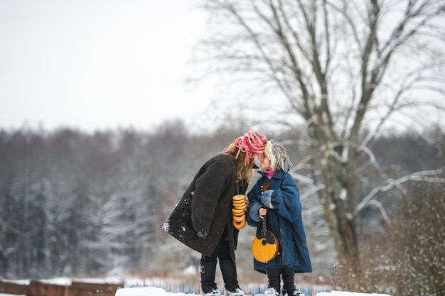 かなり白人の村の姉妹がバラライカと一緒にベンチに立っています