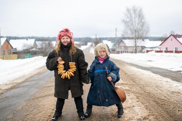 かなり白人の村の姉妹がバラライカと一緒に道路に立っています