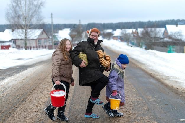 かなり白人の村の姉妹は、母親と一緒に冬に乾燥したリング状のロールサンドの笑顔で道路に立っています