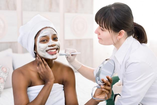 スパサロンで白いタオルでアフリカ系アメリカ人女性の顔にマスクを適用するかなり白人女性美容師