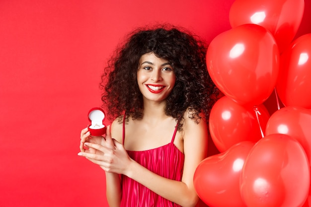 Pretty caucasian woman getting engaged on valentines day. girl receive marriage proposal on lovers holiday, showing golden ring in small box, standing near hearts balloon on red background.