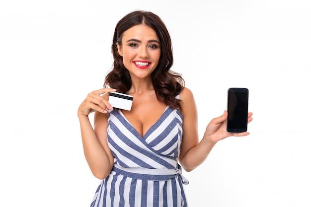 Довольно кавказская женщина держит кредитную карту и мобильный телефон, изолированные на белой стене