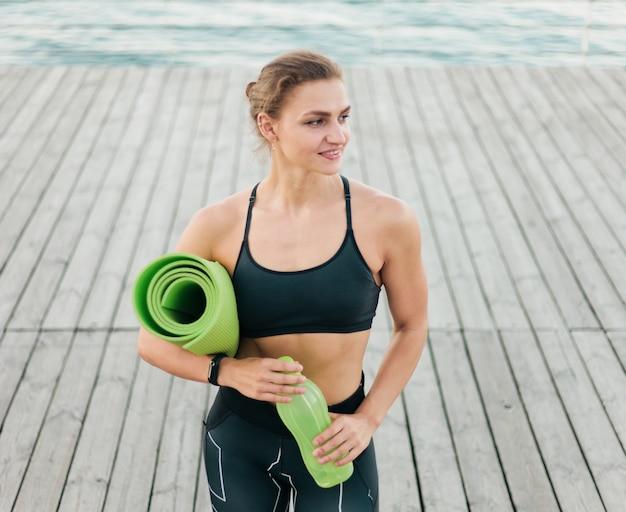 Довольно кавказская женщина в спортивной одежде держит в руках тренировочный мат и позирует на пляжной террасе