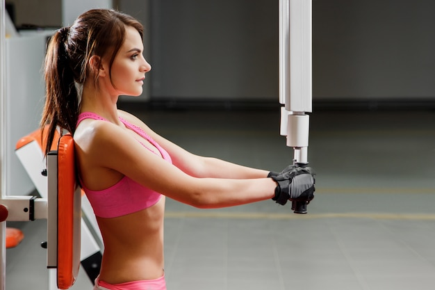 Pretty caucasian woman is working out on butterfly machine.