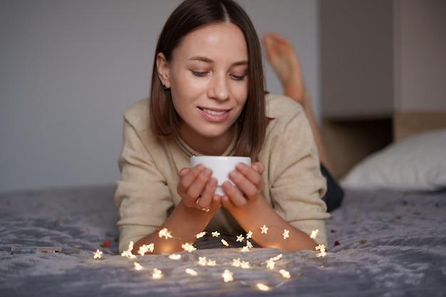 예쁜 백인 여자는 침대에 누워 요정 조명에 둘러싸여 그녀의 손에 커피와 함께 웃 고.