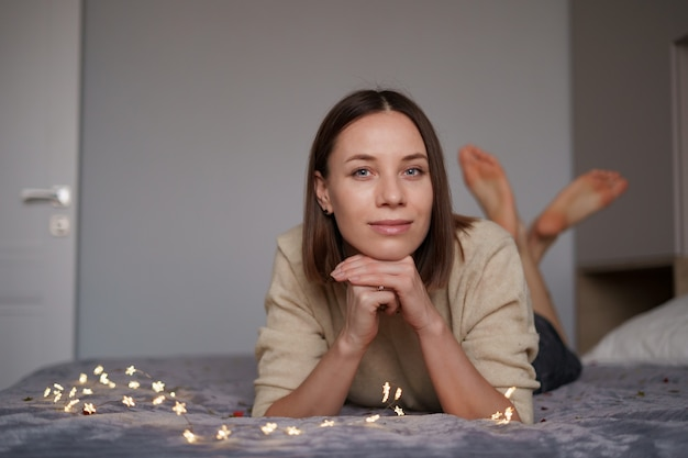Pretty caucasian woman smiling with fairy lights laying on bed.