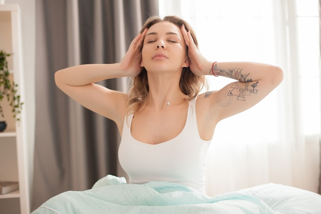 Pretty caucasian woman stretching in the morning after waking up wearing pajamas.