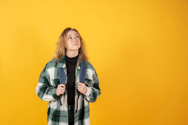 Pretty caucasian woman, traveler with backpack, thinking about traveling, yellow background, copy space