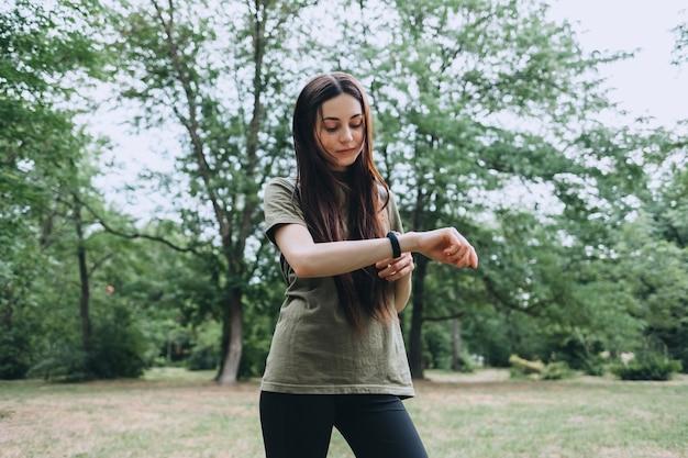 かなり白人の女性は、スポーツトレーニング中にフィットネストラッカーを使用しています。