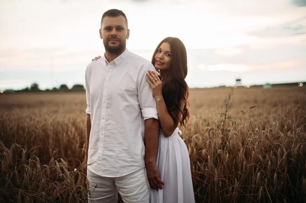 흰 드레스에 길고 어두운 물결 모양의 머리를 한 예쁜 백인 여성이 흰 티셔츠와 반바지를 입은 아름다운 남자와 포옹